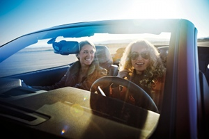 Young women drive a Ford Mustang convertible